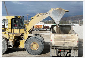 Loader filling dump truck with road base